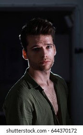 Young attractive man in opened shirt in half-shadow