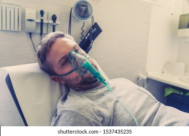 Young attractive man with oxygen mask looking sad and worried at hospital bed in clinic bedroom in lung cancer diagnose, smoking and respiratory disease and anti tobacco advertising campaign.