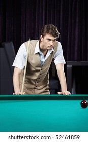 The young attractive man plays billiards