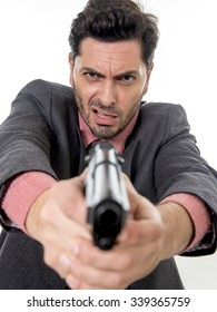young attractive man pointing gun in aggressive and upset face expression in violent assault concept