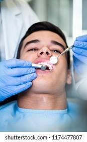 Young attractive man receiving a dental treatment. Close up shot.