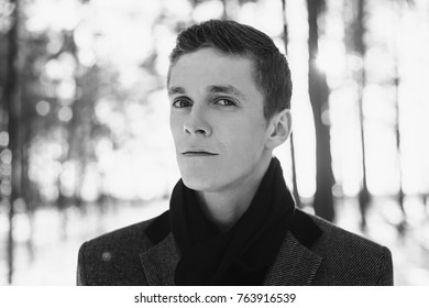 Young attractive man with short hair wearing a gray winter coat and a black scarf around his neck posing against a background of a winter forest.