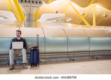 Young attractive man sitting at the airport working in his laptop waiting his flight with a suitcase.
