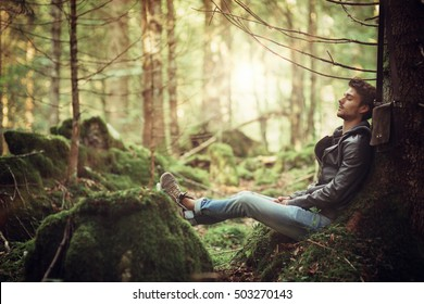 Young attractive man sitting in the forest and resting with eyes closed, relaxation and healthy lifestyle concept