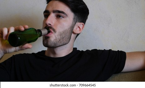 Young attractive man sitting on couch at home in living-room, drinking beer, relaxing in a lazy afternoon