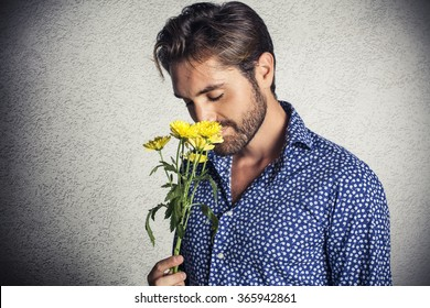 Young attractive man smelling a bunch of flowers