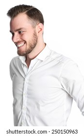 A young attractive man standing against a white background, wearing a white shirt. Feeling great with a smile on his face.