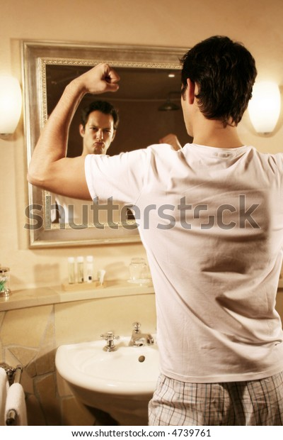a young attractive man is standing in his bath and flex one ´s muscles