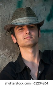 young attractive man in a straw hat against the wall, portrait
