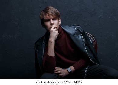 Young attractive man in a stylish leather black jacket in red golf in black jeans in trendy shoes with stylish watches posing in a dark studio near a black wall. Handsome stylish modern guy