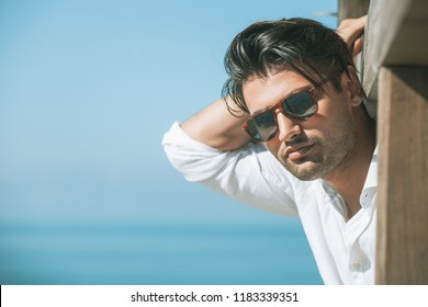 Young attractive man with sunglasses looking out over the sea during the summer. He looking forward, dressed in a white shirt and leaning on a wooden construction.
