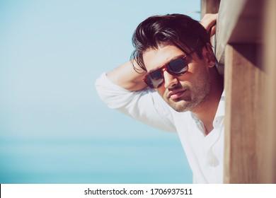 Junge attraktive Mann mit Sonnenbrille Blick über das Meer im Sommer. Er blickt nach vorn, gekleidet in einem weißen Hemd und lehnt sich auf eine Holzkonstruktion.