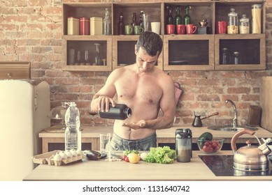 Young attractive man takes vitamin tablets for athletes in the kitchen