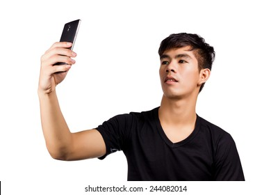 young attractive man taking pictures of him self (selfie) with smartphone isolated on white background.