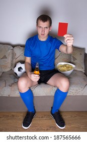 young attractive man watching football on tv at home and showing red card