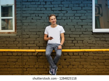 Young attractive man in white shirt with phone in the hand sitting next to the grey brick wall. Estonia. Tallinn