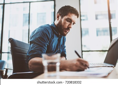 Young attractive man working at sunny loft office on laptop while sitting at wooden table.Businessman analyze digital reports on notebook computer.Blurred background,horizontal