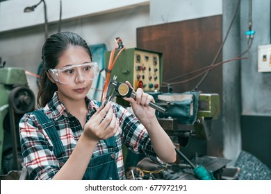 young attractive milling machining female worker wearing safety glasses working in lathe factory and using caliper scale device manufacturing parts accuracy.
