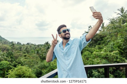 Young attractive mixed race man with a beard making selfie on the background of the sea during vacation and travel