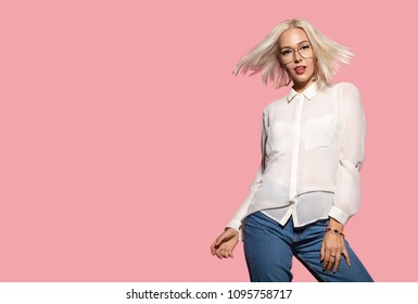 Young attractive model in motion, studio portrait. Stylish hairstyle, fashion glasses, white shirt and jeans. Beautiful blonde lady posing in studio on pink background. Concept of fashion and beauty.