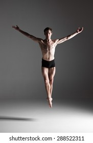 The young attractive modern ballet dancer jumping over gray background