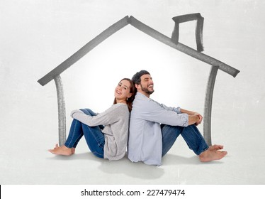 Young attractive and modern couple in love smiling happy together sitting on floor thinking and imaging their new house, home, flat or apartment in real state concept