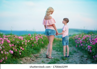 Young attractive mother hugging her son posing on camera near roses in a summer garden wearing rustic jeans and cosy dress