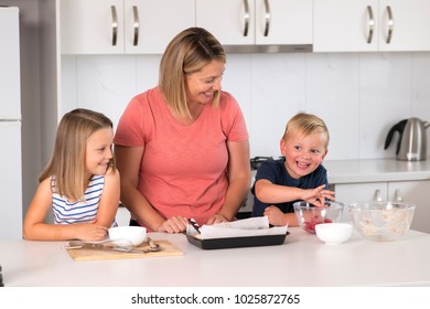 young attractive mother preparing salad together with little son and young beautiful daughter in healthy vegetable nutrition education and family lifestyle concept