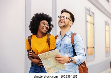 Young attractive multicultural laughing couple walking outdoors and visiting city. Man having map in his hands. Tourism concept.