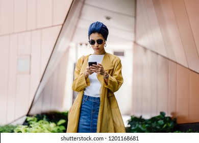 A young and attractive Muslim Malay woman wearing a stylish outfit, turban (hijab, head scarf) and sunglasses is streaming and listening to music on her phone. She is listening via wireless earphones.