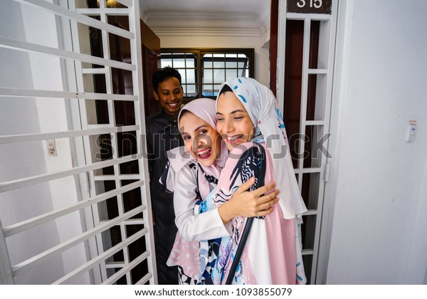 A young and attractive Muslim woman is visiting her friend's home for Raya and is greeted at the door by the couple.