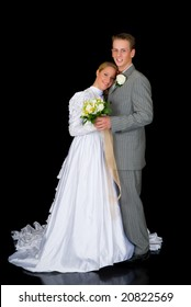 Young attractive newly wed couple.  Black background, studio shot.