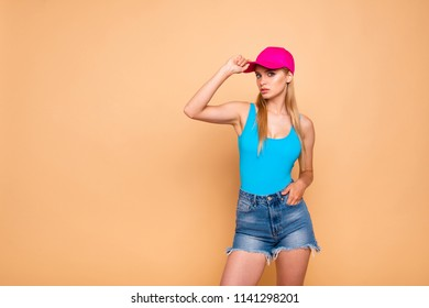 Young attractive nice cute straight-haired blonde smiling girl wearing casual, jeans denim shorts, touching bright pink sunhat, keeping hand in pocket. Copy space. Isolated over beige background