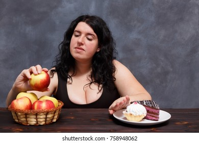 Young attractive overweight woman choosing healthy foods and giving up sweets. Dieting, healthy food, weight losing, well-being