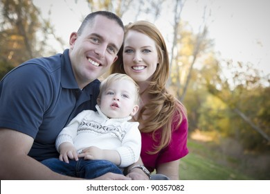 Young Attractive Parents and Child Portrait Outdoors at a Park.