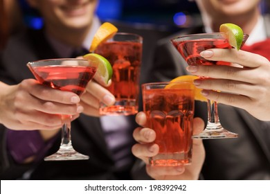 Young attractive people of four having cocktail party
