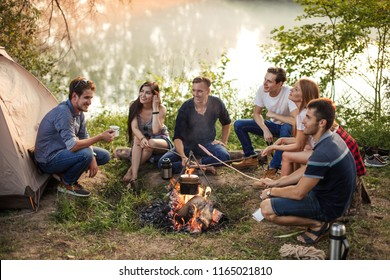 young attractive people holding sticks with sausages on the bonfire. process of preparing meal in nature. young people are huddling around the campfire