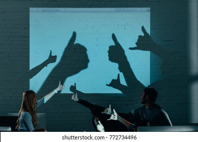 young attractive people playing with shadows after work in modern office