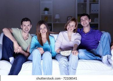 Young attractive people watch movies at home