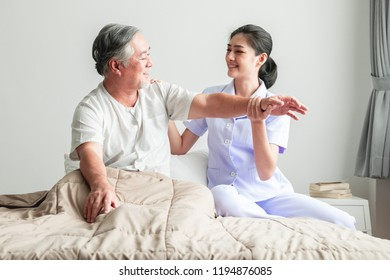 Young attractive physiotherapist working on senior man. Beautiful asian woman working with asian senior man's arm. Senior home caretaker service concept.