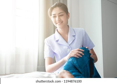 Young attractive physiotherapist working on senior man. Beautiful asian woman working with asian senior man's knee. Senior home caretaker service concept.