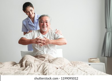 Young attractive physiotherapist working on senior man. Beautiful asian woman working with asian senior man's back. Senior home caretaker service concept.