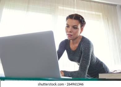 Young attractive professional business woman at office space work desk reaching and typing on her laptop computer against a bright window, working. Business finance and administrative job, interior.