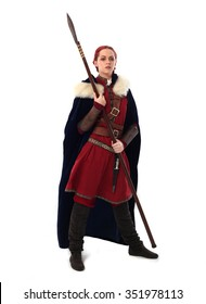 young and attractive red haired  female warrior,  wearing a red medieval tunic and leather Armour, velvet fur lined cloak. holding a spear as a weapon. isolated on a white background.