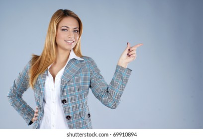 Young attractive redhead business woman over grey background