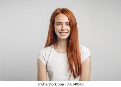 Young attractive redhead girl smiling looking at camera