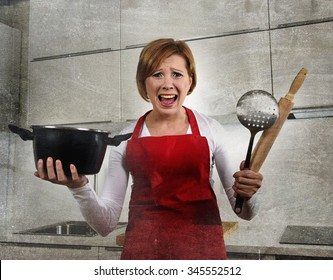 young attractive rookie home cook woman in red apron at home kitchen holding cooking pan and rolling pin screaming desperate in stress confused and helpless in lifestyle and cooking mess