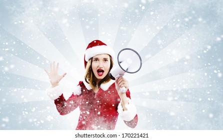 Young attractive Santa girl screaming in megaphone