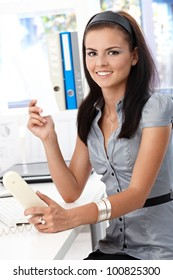 Young attractive secretary working in bright office, smiling, looking at camera.