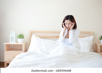 Young attractive and sexy asian woman wearing white shirt got headache on bed in white bedroom with unhappy face.